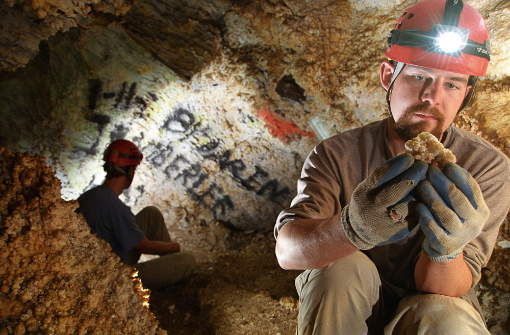 Jason Mateljak studies a broken formation in a vandalized Utah cave